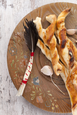breadstick: Pizza breadsticks on wooden plate on white wooden background. Culinary italian pizza eating.