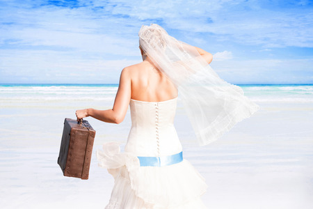 Beautiful bride with antique suitcase in white wedding dress on white sand beach with turquoise ocean on sunny day. Luxurious honeymoon, romantic wedding. photo