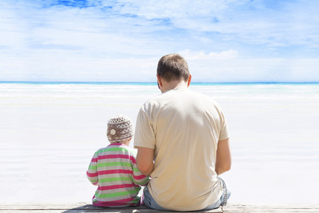 Father and daughter sitting on empty white sand beach with turquoise ocean on sunny day. Relationship, family, lifestyle, fatherhood, togetherness.