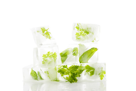 Culinary aromatic cooking herbs basil and parsley frozen in ice cubes isolated on white background. Fresh healthy cooking.  photo