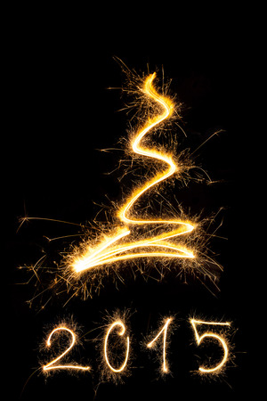 Merry christmas and happy new year 2015. Sparkling firework christmas and new year text on black background. Minimal abstract artistic style. photo