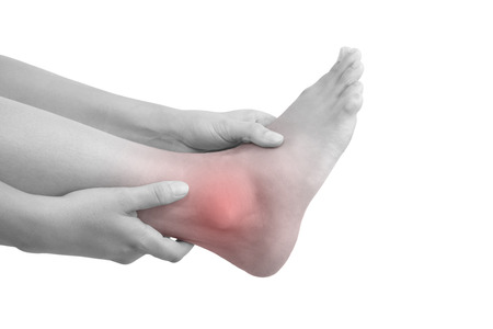 muscle strain: Sprained ankle, muscle injuries and muscle strain. Female hand holding leg with highlighted pain area isolated on white background.