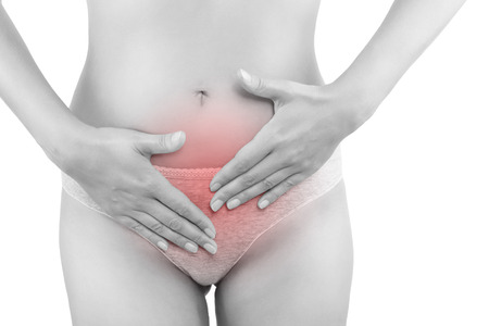 Beautiful woman touching her belly in grey panties isolated on white background. Menstruation, period, pregnancy. Feminine health problems.