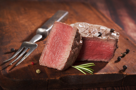 rare: Juicy steak on dark wooden background. Luxurious mignon steak, rare. Culinary red meat eating.