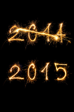 strikethrough: Strikethrough 2014 and 2015 digits made of sparkling light isolated on black background. Old year going, new year comming. Stock Photo