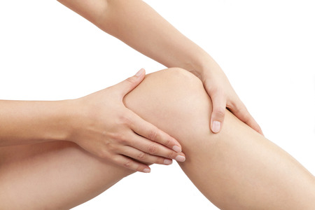 muscle strain: Female hand holding knee isolated on white background. Knee injury, muscle strain, sport injury.