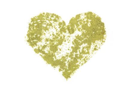 Chlorella, spirulina and wheat grass ground powder forming heart shape. Detox, healthy living, alternative medicine. photo
