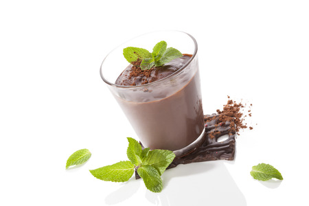 Chocolate pudding with fresh mint leaves and chocolate bar isolated on white background. Culinary sweet dessert.