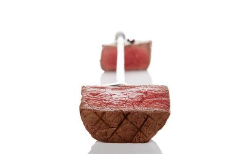 carnes rojas: Steak pieza de tenedor aisladas sobre fondo blanco. Filete de solomillo raro, culinario comer carne roja.
