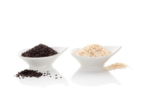 white sesame seeds: Black and white sesame seeds isolated on white background. Culinary healthy food ingredient. Stock Photo