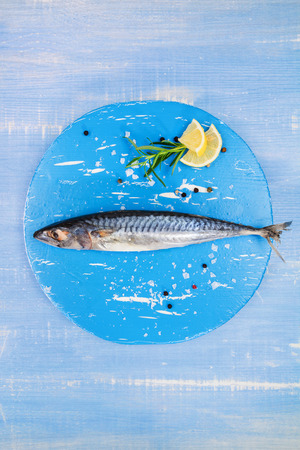 Mediterranean seafood concept. Fresh mackerel fish on blue wooden plate with lemon and rosemary on blue wooden textured background. photo