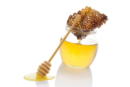 comp: Luxurious organic honey in glass jar, honey comp and honey spoon isolated on white background. Healthy honey eating. Stock Photo