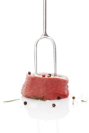 carne roja: Filet mignon Raw en bistec tenedor con hierbas y granos de pimienta aislados sobre fondo blanco. Lujoso carne roja carne comer. Foto de archivo