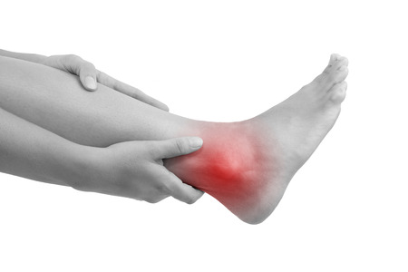 Sprained ankle, muscle injuries and muscle strain. Female hand holding leg with highlighted pain area isolated on white background.