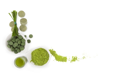 detox: Greed superfood. Spirulina, chlorella and wheat grass ground powder, effervescent tablets, grass blades isolated on white background, top view. Detox and healthy living.