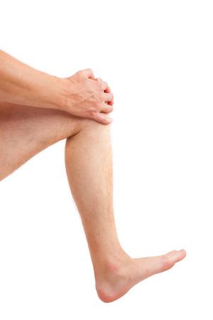 piernas hombre: Hombre hermoso que sostiene su rodilla herida aislada en el fondo blanco. Lesi�n en la rodilla. Foto de archivo