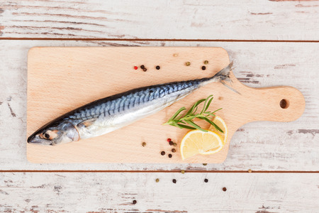 Delicious fresh mackerel fish on wooden kitchen board with lemon, rosemary and colorful peppercorns on white textured wooden background. Culinary healthy cooking. photo