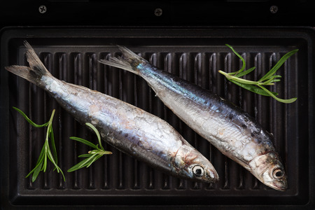 anchovy fish: Two fresh anchovy fish on black roast, top view. Barbeque, roasted seafood concept. Delicious healthy eating.