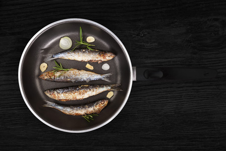 anchovy fish: Delicious fresh anchovy fish with fresh rosemary herbs on pan on black wooden background. Culinary healthy seafood cooking. Stock Photo