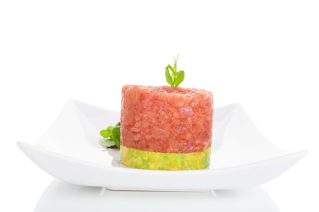 steak tartare: Delicious tuna steak tartare with avocado dip and fresh green salad on plate on white background. Fine dining.