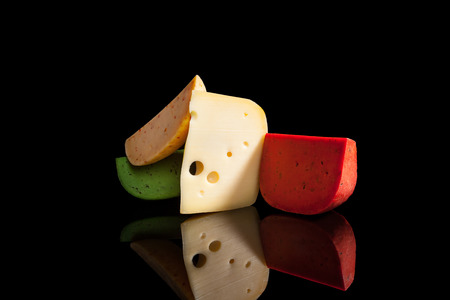 cheeseboard: Luxurious cheese variation on black background. Leerdammer and various flavoured gouda cheese on black background with reflection. Stock Photo