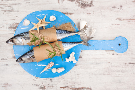 Delicious fresh mackerel fish on wooden kitchen board with sea shells and sand on white textured wooden background. Culinary healthy cooking. photo