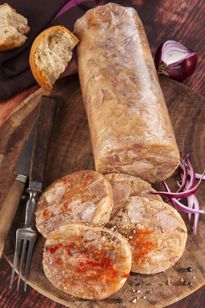 brawn: Head cheese cold cut vintage background. Brawn with onion and bread on wooden vintage chopping board. Stock Photo