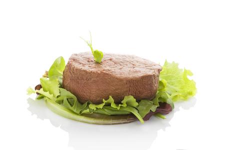 carnes rojas: Filete grande en la ensalada verde aislado sobre fondo blanco. Culinario comer bistec. Filet mignon, filete de lomo. Carne roja. Foto de archivo