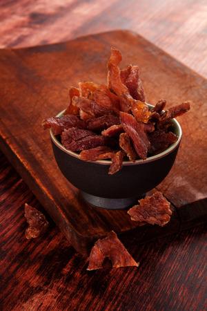 stile country: Beef scatti. Carne secca a scatti di manzo sul tagliere di legno su sfondo di legno. Carne secca, in stile rustico. Delicious mangiare carne.