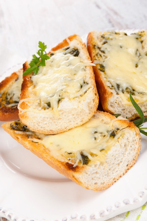 Garlic baguette with melted cheese on white wooden background. Culinary eating. photo