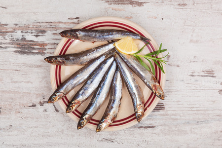 Several sardines on plate, on white wooden background, top view. Mediterranean seafood eating. photo