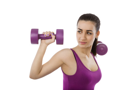 Beautiful girl with purple top and purple dumbbells isolated on white background. Sport and fitness, healthy living. photo