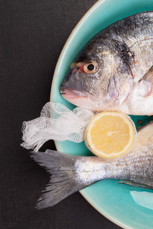 Delicious sea bream with lemon on turquoise plate on black background, top view. Mediterranean seafood background. photo
