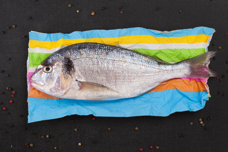 sea bream: Delicious fresh sea bream fish on colorful napkin with colorful peppercorns on black textured stone table. Culinary healthy cooking. Stock Photo
