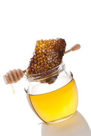 honey comb: Honey in glass jar with wooden honey spoon and honey comb on white background. Healthy honey eating.