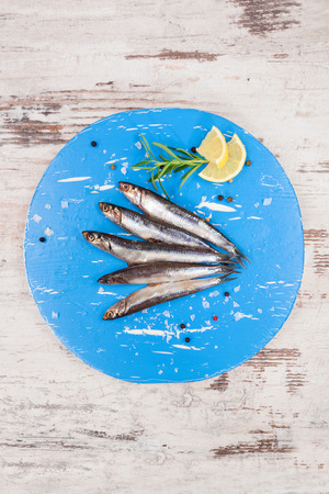 blue white kitchen: Several sardines on blue round kitchen board, on white wooden background, top view. Mediterranean seafood eating.