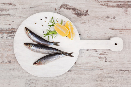 european anchovy: Three fresh anchovy fish on white round kitchen board on white wooden table, top view. Culinary seafood concept. Delicious healthy eating.