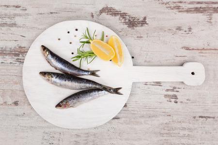 mariscos: Tres pescados frescos de anchoa en blanco tablero de cocina redonda en la mesa de madera blanca, vista desde arriba. Concepto de mariscos culinario. Alimentaci�n saludable delicioso. Foto de archivo