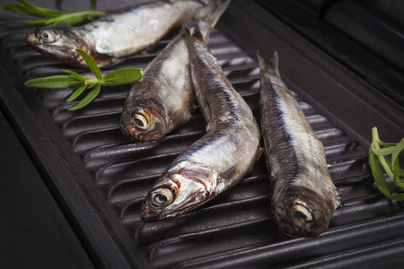 anchovy fish: Fresh anchovy fish on black roast. Barbeque, roasted seafood concept. Delicious healthy eating.