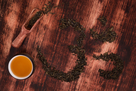 ohm: Traditional tea drinking. Cup of tea, dry tea leaves forming ohm symbol and wooden scoop on wooden background, top view.