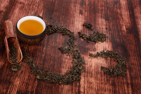 ohm: Cup of tea, dry tea leaves forming ohm symbol and buddhist necklace. Traditional tea drinking.