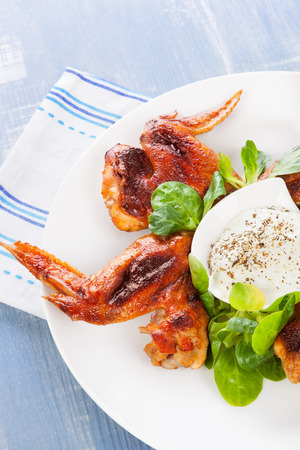 american cuisine: Delicious buffalo wings with fresh salad and dressing on plate on blue wooden background. Culinary american cuisine.