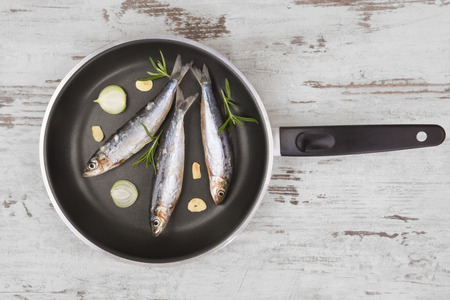 anchovy fish: Fresh anchovy fish on black pan on white textured wooden background. Culinary seafood eating, mediterranean style.