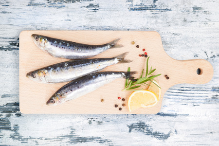 european anchovy: Three fresh anchovy fish on wooden kitchen board on white and blue wooden table, top view. Culinary seafood concept. Delicious healthy eating.