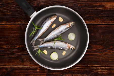 anchovy fish: Fresh anchovy fish on black pan on aged brown textured wooden background. Culinary seafood eating, rustic style. Stock Photo