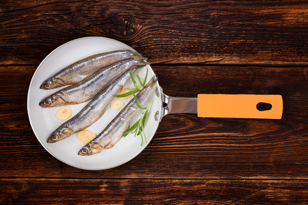 Fresh sardines with garlic and fresh herbs on pan on wooden background, top view. photo