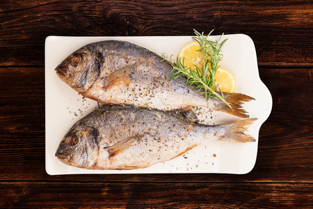 sea bream: Delicious grilled sea bream fish on kitchen board with rosemary, lemon and colorful peppercorns on brown textured wooden background. Culinary healthy cooking.