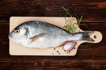 sea bream: Delicious fresh sea bream fish on wooden kitchen board with onion, rosemary and colorful peppercorns on white textured wooden background. Culinary healthy cooking. Stock Photo
