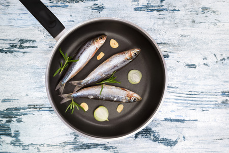 anchovy fish: Fresh anchovy fish on black pan on blue and white textured wooden background. Culinary seafood eating, mediterranean style. Stock Photo