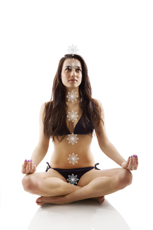 enlightenment: Beautiful girl sitting in lotus position with seven chakras isolated on white background. Consciousness, enlightenment and yoga. Stock Photo